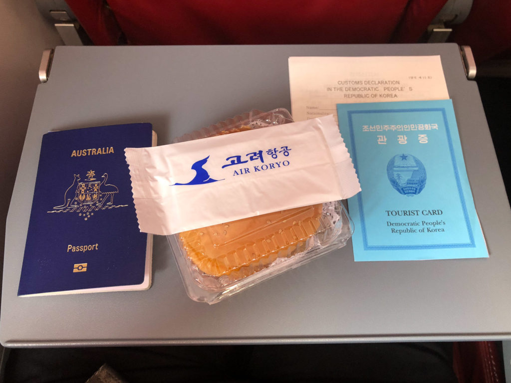 North Korea tourist card and Air Koryo burger on the flight to Pyongyang